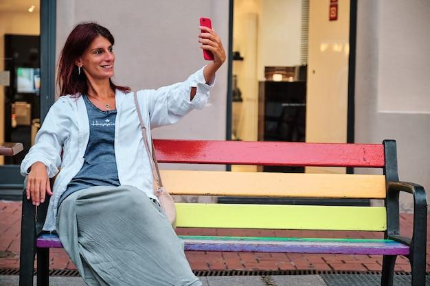 Dorosła kobieta na ławce za pomocą telefonu komórkowego