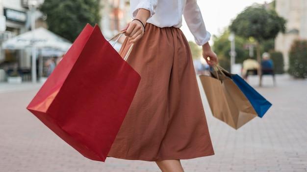 Dorosła kobieta niosąca kolorowe torby na zakupy