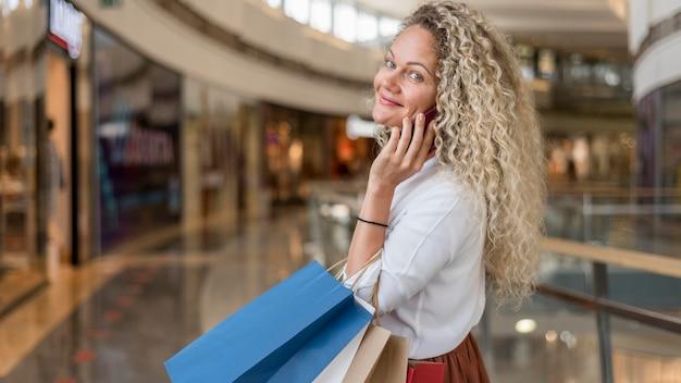 Dorosła kobieta niosąca torby na zakupy w centrum handlowym