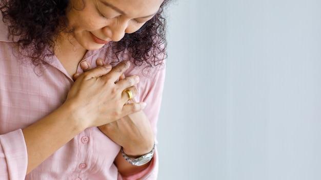 Dorosła kobieta odczuwa ból i używa dotyku i trzymania na klatce piersiowej dotkniętej zastoinową niewydolnością serca lub resuscytacją krążeniowo-oddechową.