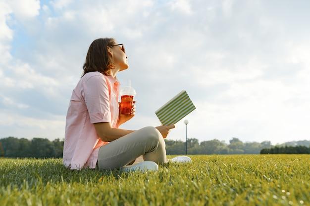 Dorosła kobieta odpoczywa w parku, siedzi na trawie z książką