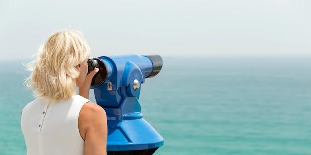 Dorosła kobieta patrząc przez lornetkę na krajobraz morski