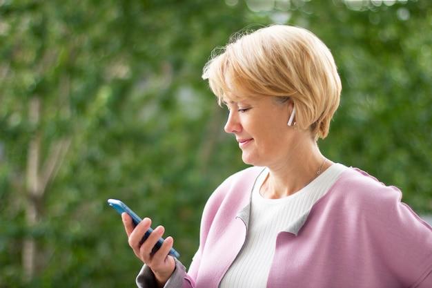 Dorosła kobieta patrzeje smartphone, ono uśmiecha się.