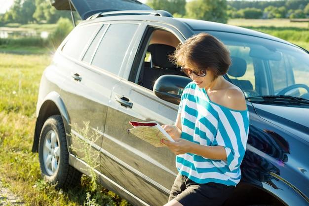 Dorosła kobieta patrzeje w turystyczną mapę blisko samochodu