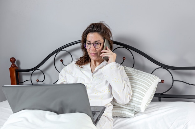 Dorosła kobieta pracuje w domu w pijama