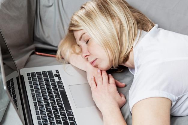 Dorosła kobieta rasy białej śpi przed otwartym laptopem na kanapie z szarą pościelą. stres związany z dodatkowymi godzinami pracy może mieć negatywny wpływ na zdrowie.