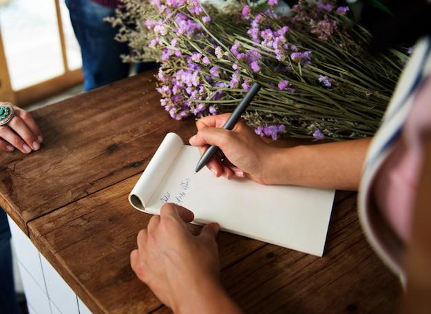 Dorosła kobieta ręka pisze rozkaz notatce