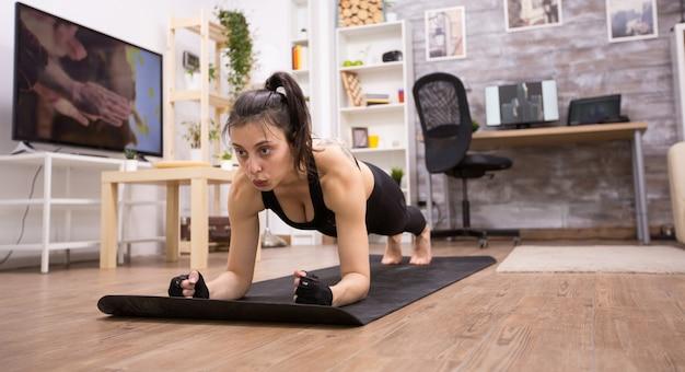 Dorosła kobieta robi ćwiczenia deski, aby poprawić jej sprawność fizyczną. dopasowana kobieta.