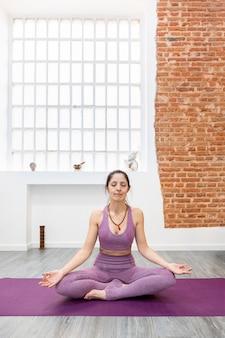 Dorosła kobieta robi ćwiczenia jogi i medytacji w nowoczesnym mieszkaniu. miejsce na tekst.