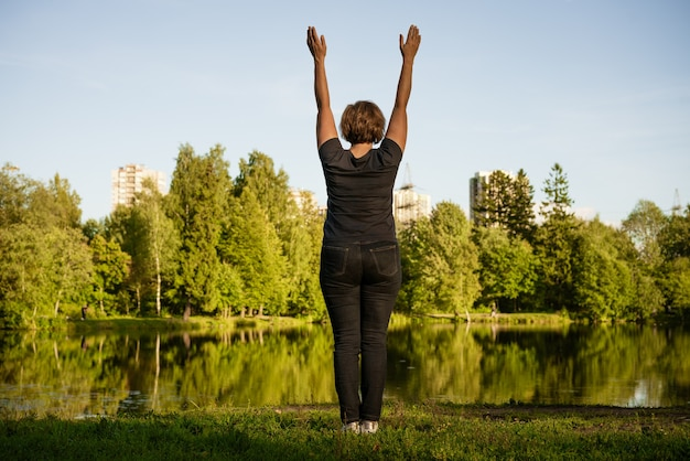 Dorosła kobieta robi ćwiczenia nad jeziorem w parku w letni dzień