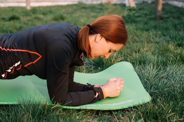 Dorosła kobieta robi deski ćwiczeniu w parku