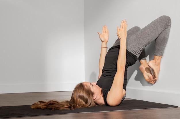 Dorosła kobieta robi joga w domu