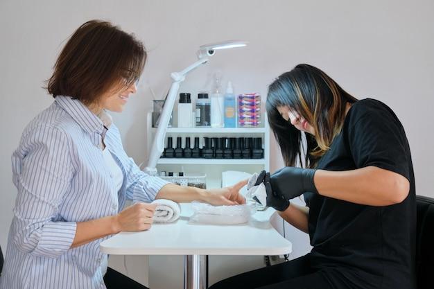 Dorosła kobieta robi manicure w salonie do pielęgnacji dłoni i paznokci