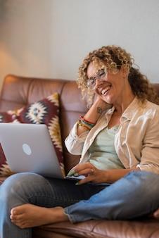 Dorosła kobieta siada na kanapie w domu i korzysta z wideokonferencji z przyjaciółmi, uśmiechając się i rozmawiając na laptopie - ludzie online i połączenie bezprzewodowe