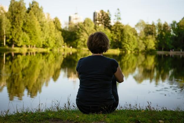 Dorosła kobieta siedząca nad jeziorem odwróciła się plecami