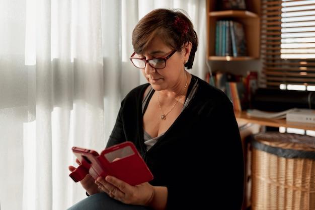 Dorosła kobieta siedząca w piżamie z krótkimi włosami za pomocą smartfona w pokoju studio, pozostając w domu z powodu kwarantanny.