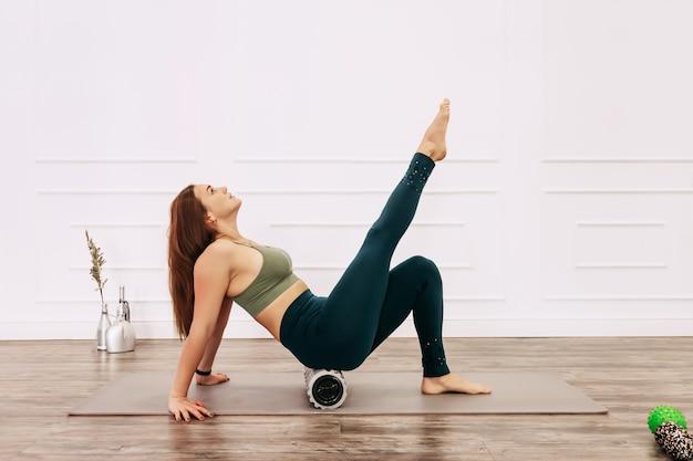 Dorosła kobieta sportowy robi ćwiczenia powięzi na podłodze. fizjoterapia i koncepcja stretch szkolenia