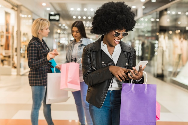 Dorosła kobieta sprawdza jej telefon komórkowego przy centrum handlowym