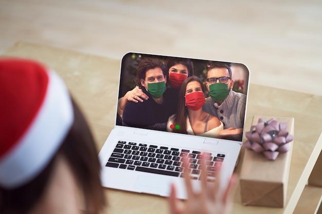 Dorosła kobieta świętująca boże narodzenie w domu i prowadząca wideorozmowę z przyjaciółmi