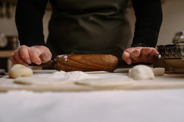 Dorosła kobieta toczy ciasto w kuchni, aby przygotować pieczenie lub pierogi, manti