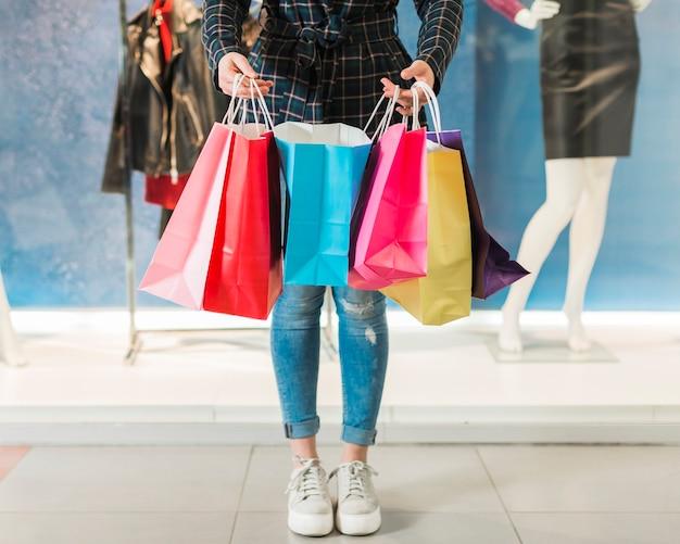 Dorosła kobieta trzyma kolorowe torby