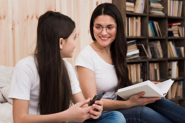 Dorosła kobieta trzyma książkę i ono uśmiecha się przy dziewczyną