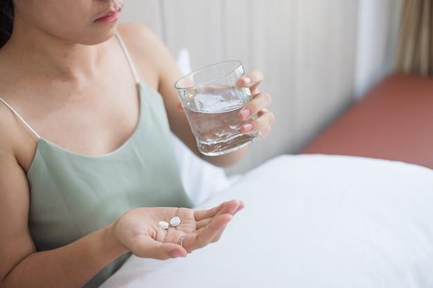 Dorosła kobieta trzyma pigułkę i szklankę wody, biorąc lek na łóżku rano w domu. migrena, lek przeciwbólowy, ból głowy, grypa, choroba, choroba i pojęcie opieki zdrowotnej