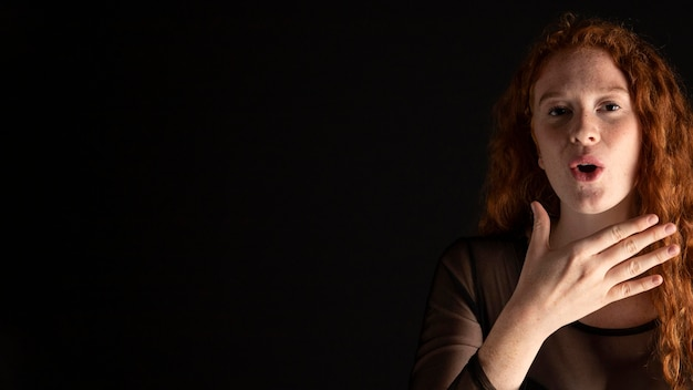 Dorosła kobieta uczy języka migowego z miejsca na kopię