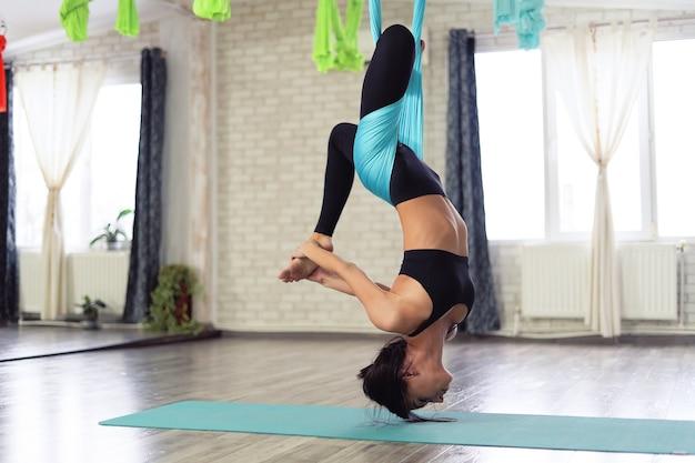 Dorosła kobieta uprawia jogę antygrawitacyjną