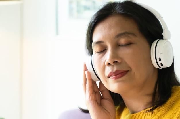Dorosła kobieta używa białych słuchawek bezprzewodowych do słuchania muzyki w domu