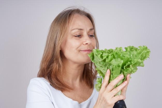 Dorosła kobieta w białej koszuli trzyma bukiet zielonej sałatki