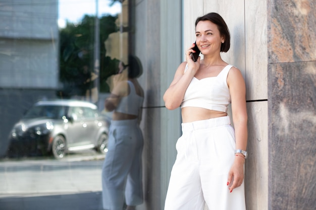 Dorosła kobieta w białym garniturze rozmawia przez telefon, stojąc na ulicy i patrząc w bok na tle nowoczesnego szkła. miejsce na twój projekt