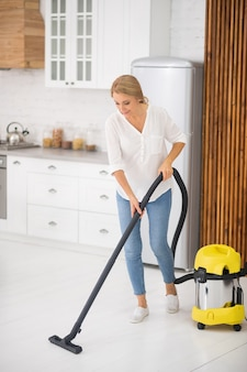 Dorosła kobieta w bluzce i dżinsach odkurzanie białej podłogi w domu w kuchni