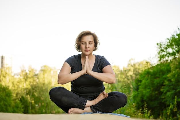 Dorosła kobieta w ciemnym ubraniu w pozycji lotosu medytuje w parku w promieniach słońca