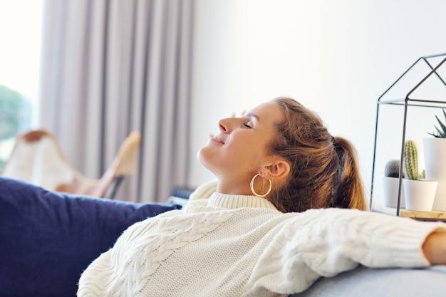 Dorosła kobieta w ciepłym swetrze odpoczywa w domu pewnego jesiennego dnia