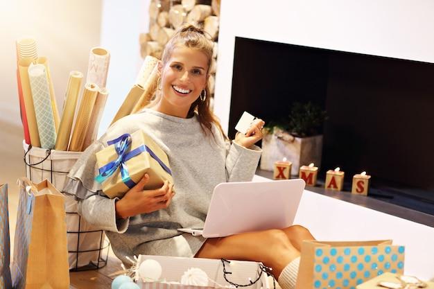 Dorosła kobieta w domu pakuje świąteczne prezenty