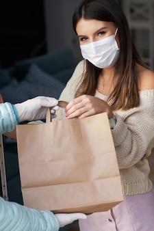 Dorosła kobieta w kwarantannie z maską na twarz dostaje dostawę jedzenia do domu