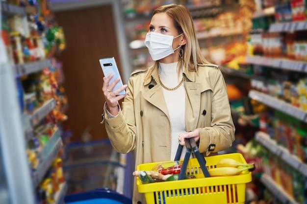 Dorosła kobieta w masce medycznej, korzystająca ze smartfona i robiąca zakupy spożywcze
