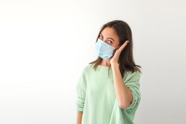 Dorosła kobieta w masce medycznej trzymająca dłoń w pobliżu ucha i patrząc na kamerę, udając, że dzwoni podczas pandemii