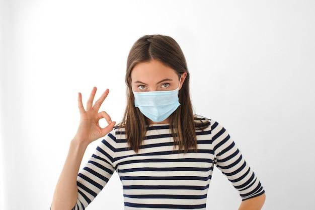 Dorosła kobieta w pasiastej koszulce i masce medycznej oraz gestykulująca ok podczas epidemii