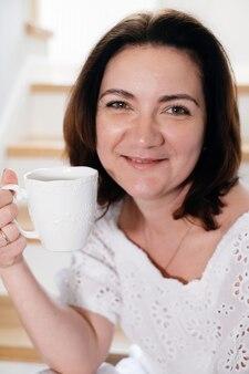 Dorosła kobieta w średnim wieku plus rozmiar siedząca rano na schodach