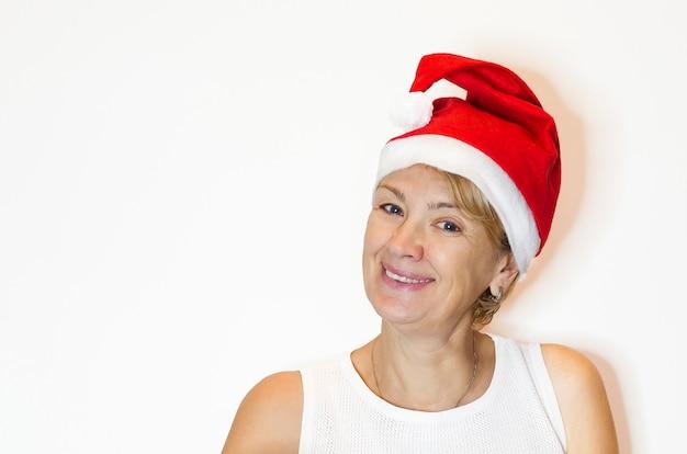 Dorosła kobieta w średnim wieku w czapce świętego mikołaja na nowy rok i boże narodzenie.