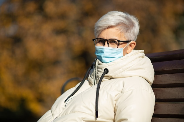 Dorosła kobieta w wieku siedząca na ławce w parku jesienią ubrana w maskę medyczną