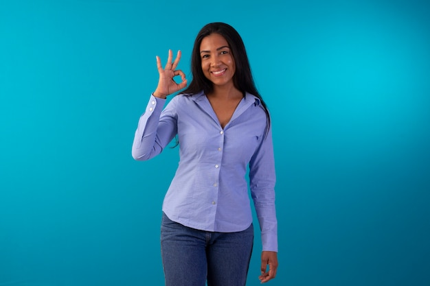 Dorosła kobieta w wizytowym stroju, ubrana w niebieską koszulę i dżinsy na zdjęciu studyjnym na niebieskim tle.