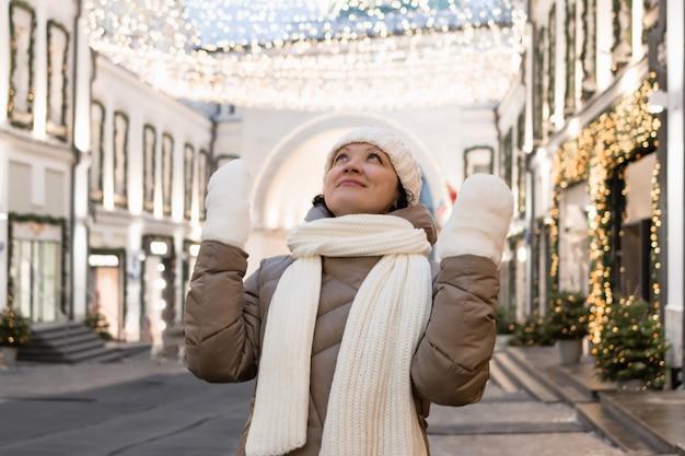 Dorosła kobieta w zimowym stroju na mieście patrzy na bożonarodzeniową iluminację i podziwia to, co widzi.