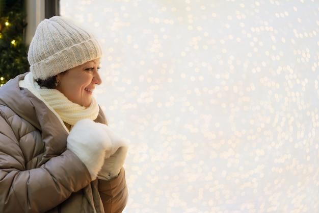 Dorosła kobieta w zimowym ubraniu patrzy na świąteczną wystawę sklepową z oświetleniem i cieszy się z tego, co widzi.