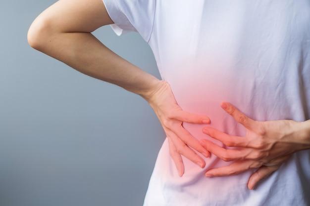 Dorosła kobieta z bólem mięśni na szarym tle. starsza kobieta cierpiąca na ból pleców z powodu zespołu gruszkowatego mięśnia gruszkowatego, bólu krzyża i ucisku kręgosłupa. urazy sportowe i koncepcja medyczna