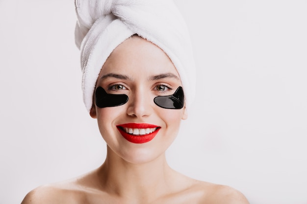 Dorosła kobieta z czerwoną szminką uśmiecha się podczas zabiegu spa. atrakcyjna pani ze zdrową skórą pozuje z łatami pod oczami.