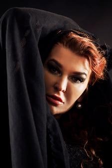 Dorosła kobieta z czerwonymi włosami na czarnym tle