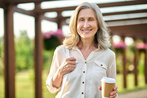 Dorosła kobieta z kawą, ciesząca się spacerem w parku
